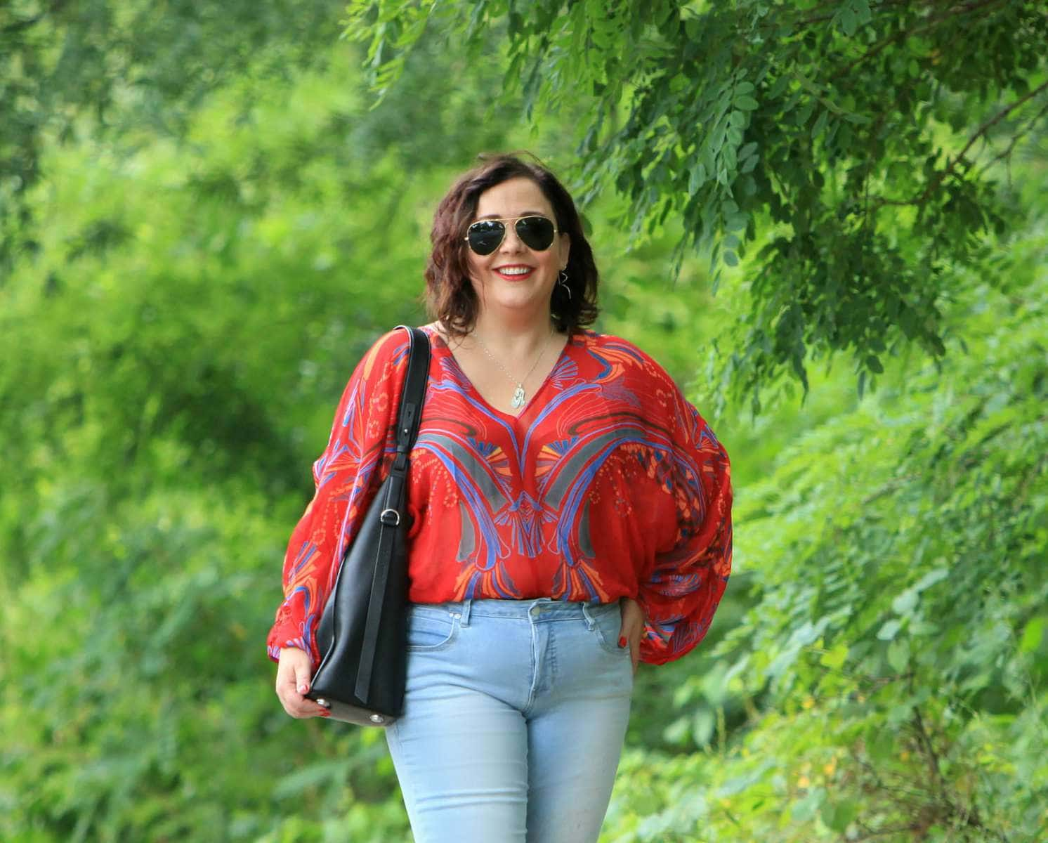 Alison Gary of Wardrobe Oxygen standing with hand on her hip, smiling. She is wearing a red printed blouse and light denim jeans with aviator sunglasses