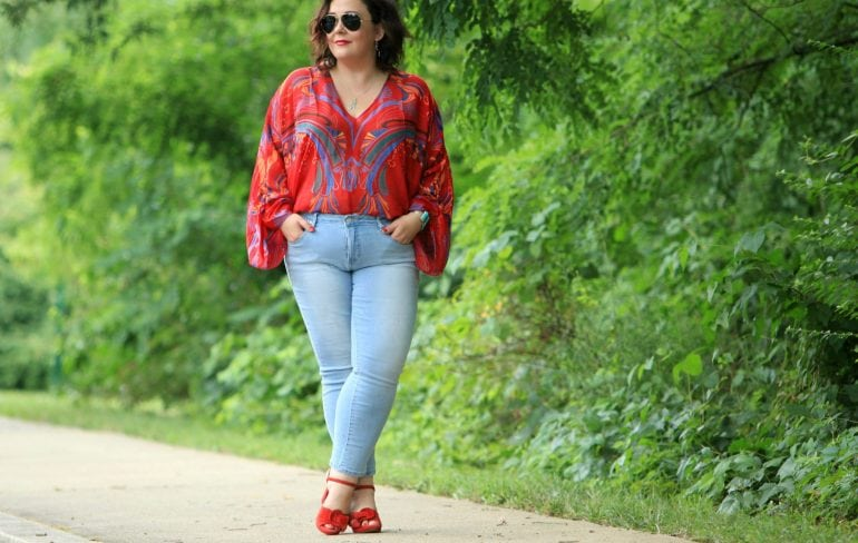 Alison Gary of Wardrobe Oxygen wearing a red printed chiffon blouse from Free People with light wash ankle jeans, carrying a black leather tote bag and wearing red suede platform heeled sandals