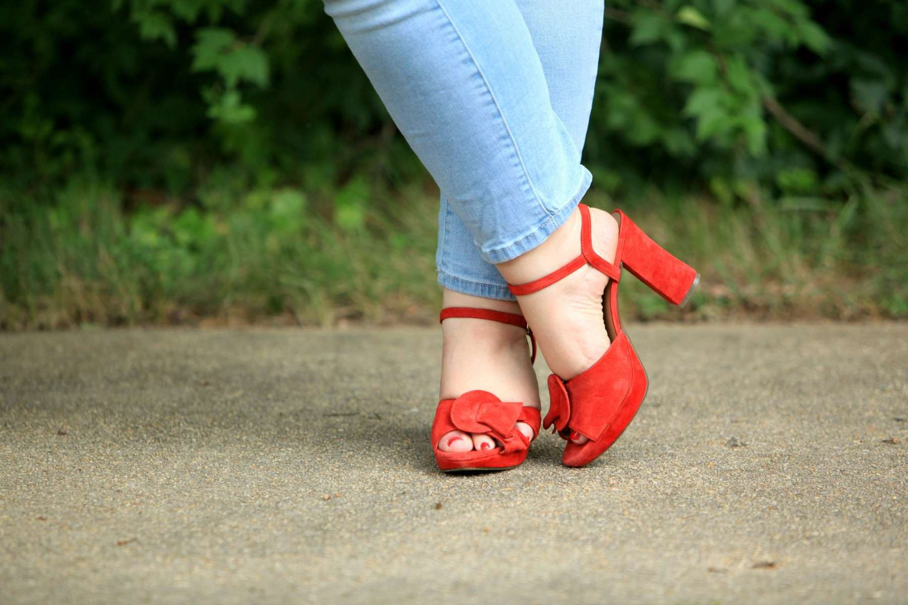 Picture of feet, ankles crossed. The legs are in light wash ankle length jeans, on the feet are red suede ankle strap block heel platform sandals.