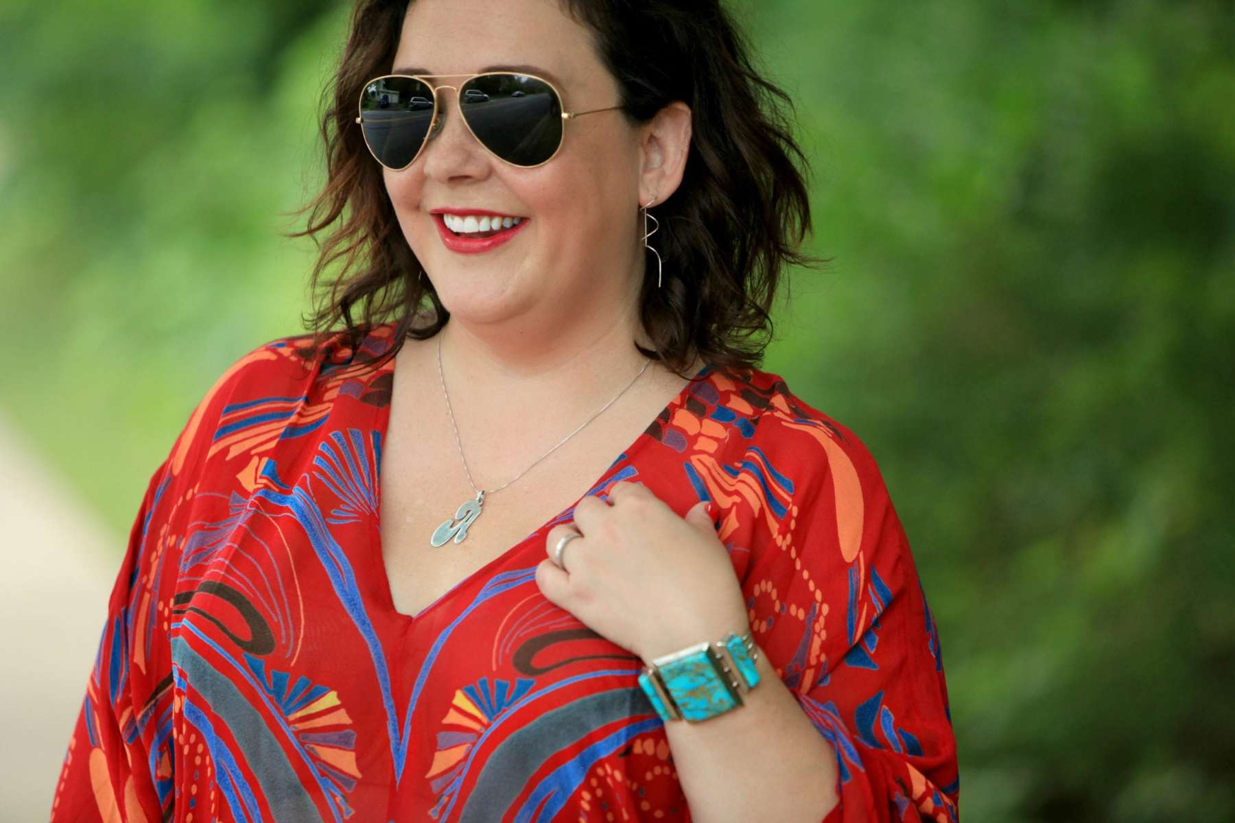 Closeup of Alison Gary smiling away from the camera. She is wearing dark aviator sunglasses, a red printed v neck blouse, and a turquoise and sterling silver cuff bracelet.