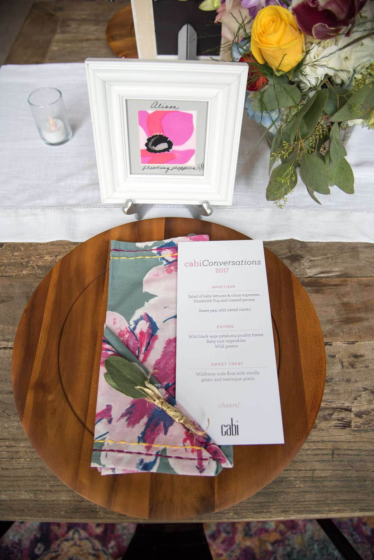 photo of a wood platter with a menu on top of it. Behind it is a square picture frame with a poppy painting inside, and the name Alison written in script above the poppy