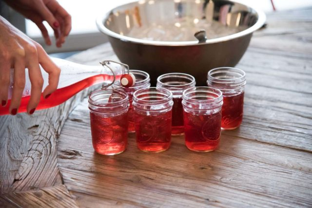 hibiscus collins cocktail being poured from a bottle into mason jars