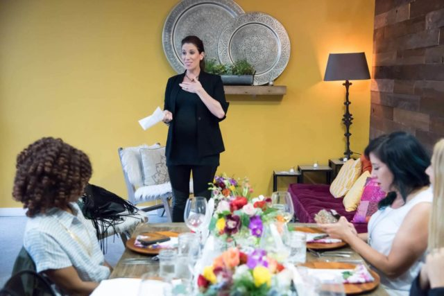 Katie Malone, VP of Marketing for cabi standing in front of a room with people sitting at tables listening to her speak