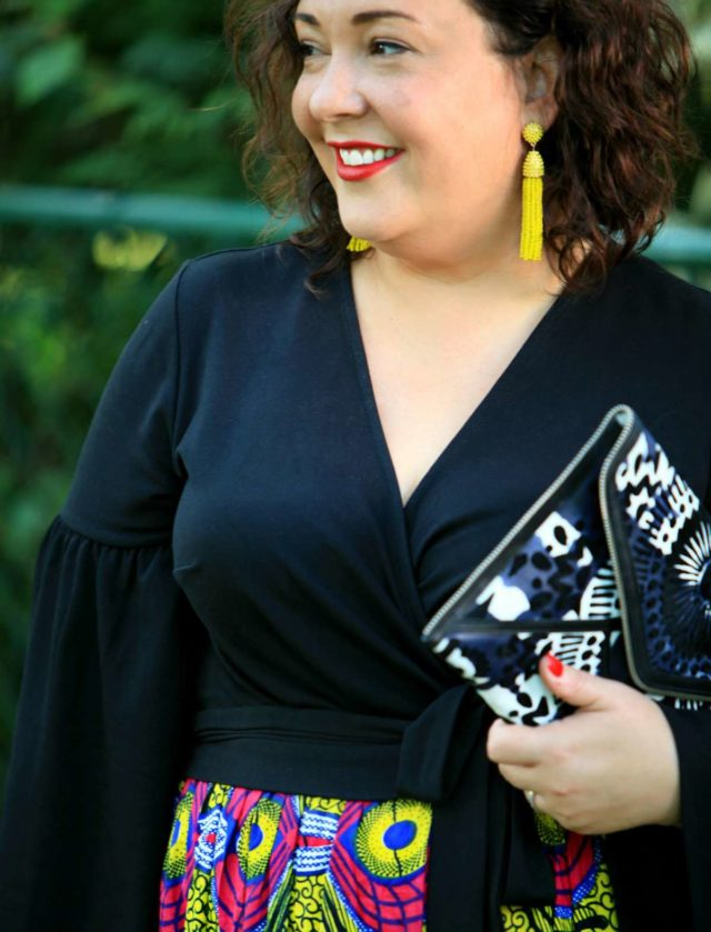 Wardrobe Oxygen in Baublebar tassel earrings, an ELOQUII wrap top, and Rebecca Minkoff clutch
