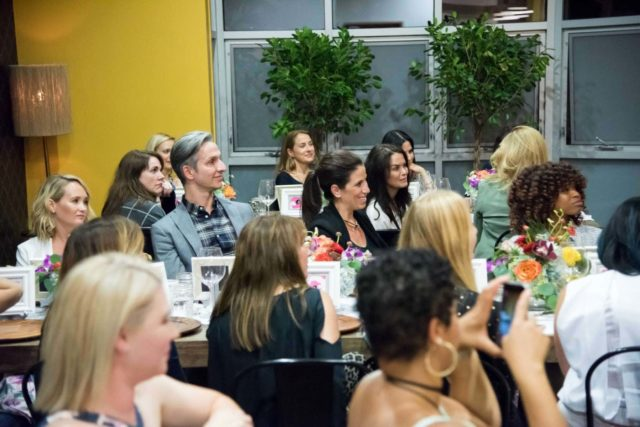 photo is of several people sitting at tables smiling and looking at someone who is off camera.