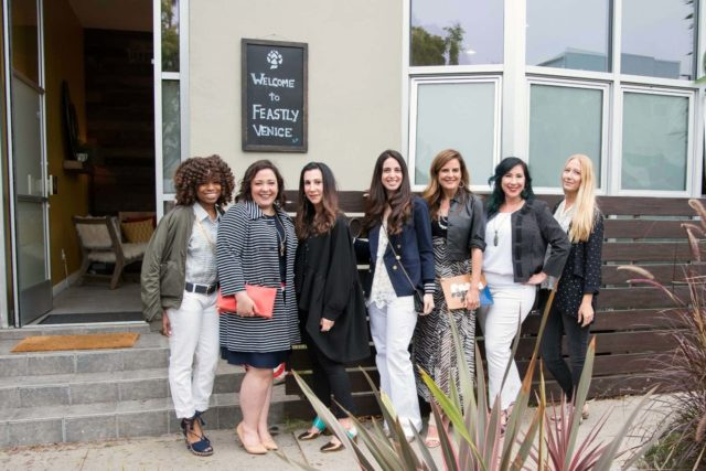 Seven bloggers standing outside a building with a sign on it that says Welcome to Feastly.