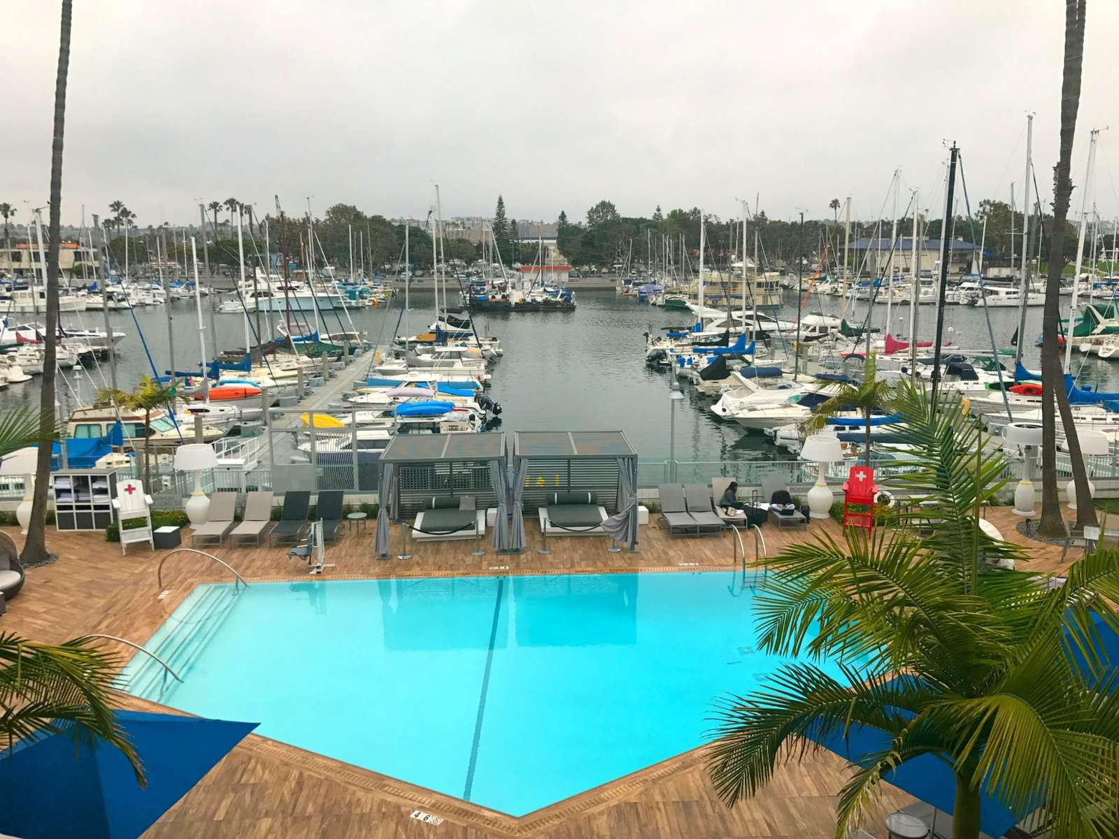 view of the marina from a window at the marina del rey hotel. in the picture are several boats in a marina and a swimming pool
