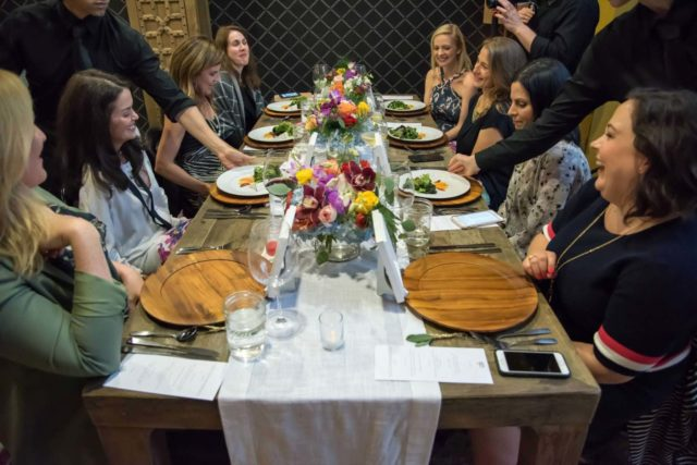 a table with eight women sitting at it laughing and speaking