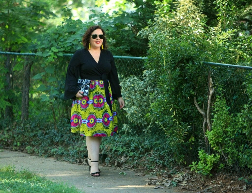 Wardrobe Oxygen in an ELOQUII wrap top with bell sleeves and an yellow Ankara midi skirt
