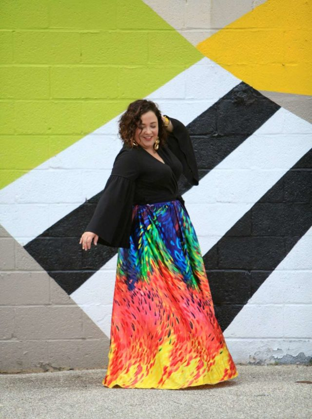 Wardrobe Oxygen in an ELOQUII wrap top, custom made rainbow maxi skirt from Trinity Michelle, and vintage gold earrings