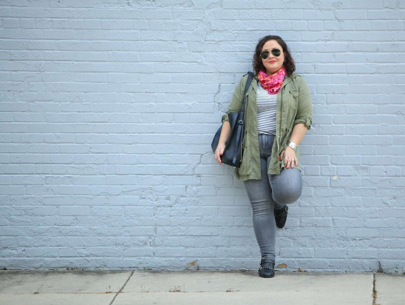 wardrobe oxygen in grey jeans and an olive utility jacket