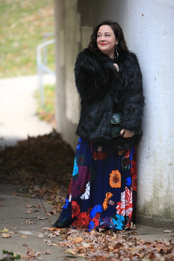 Wardrobe Oxygen in an ELOQUII dark floral maxi dress with an Elloq black faux fur coat and Clare V green crocs clutch