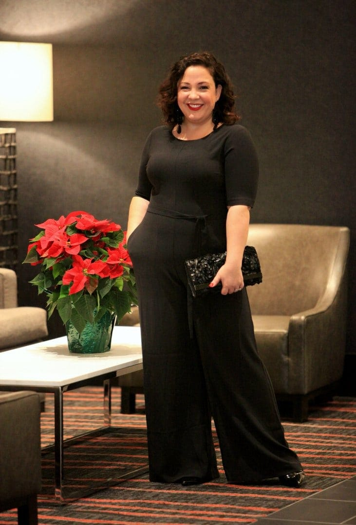 Wardrobe Oxygen in a Simply Vera Vera Wang jumpsuit, earrings, and clutch dressed for a cocktail party
