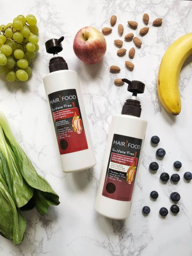 Bottle of Hair Food Color Protect Shampoo and Conditioner on a table surrounded by fruits and vegetables and nuts