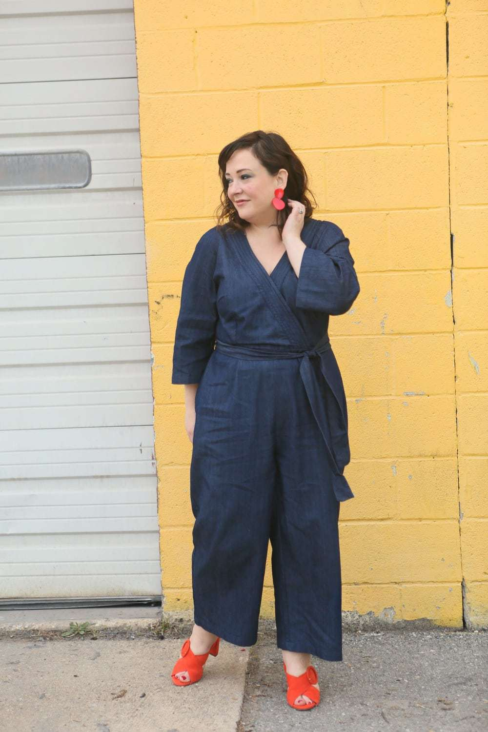 Wardrobe Oxygen in a denim wrap style jumpsuit from ELOQUII with orange suede Ann Taylor heeled sandals and red lucite statement earrings - ELOQUII Denim Jumpsuit styled by popular Washington DC petite fashion blogger, Wardrobe Oxygen