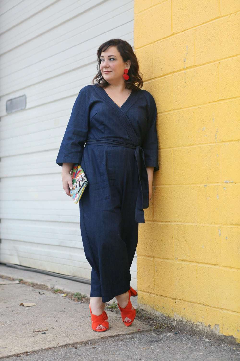 Wardrobe Oxygen in a plus size denim jumpsuit from ELOQUII with orange sandals and red lucite statement earrings - ELOQUII Denim Jumpsuit styled by popular Washington DC petite fashion blogger, Wardrobe Oxygen