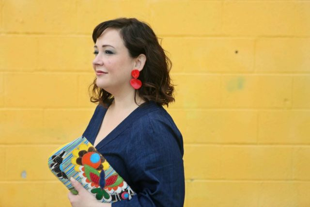 Wardrobe Oxygen in red lucite statement earrings from Nordstrom and a recycled patterned clutch bag from Novica - ELOQUII Denim Jumpsuit styled by popular Washington DC petite fashion blogger, Wardrobe Oxygen