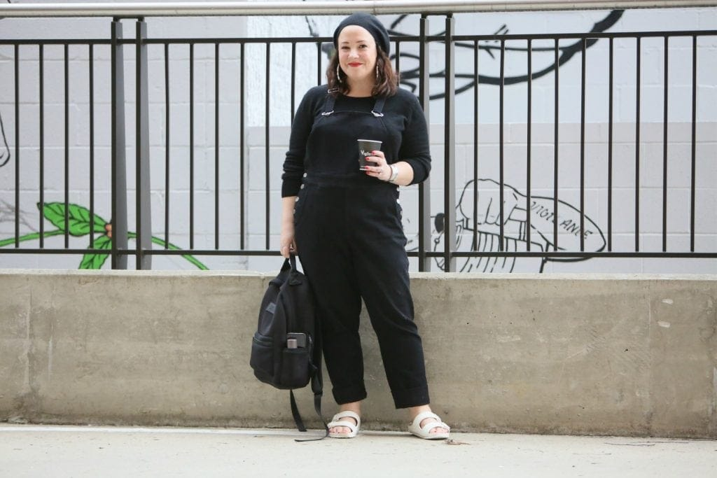 Universal Standard black overalls with a black cashmere sweater, EVA Birkenstocks, and the Dagne Dover Dakota backpack on Wardrobe Oxygen