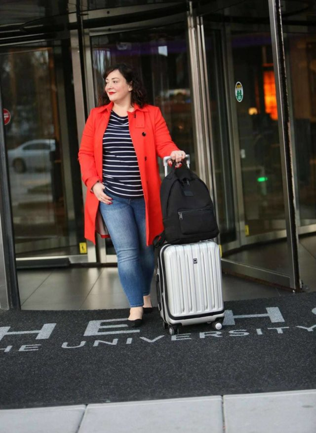 Wardrobe Oxygen in a red orange trench from Banana Republic with Talbots striped top, Banana Republic ankle jeans, Rothy's flats, Dagne Dover backpack and Delsey spinner suitcase