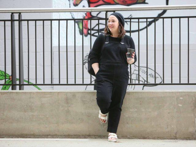Universal Standard black overalls with a black cashmere sweater, EVA Birkenstocks, and the Dagne Dover Dakota backpack on Wardrobe Oxygen