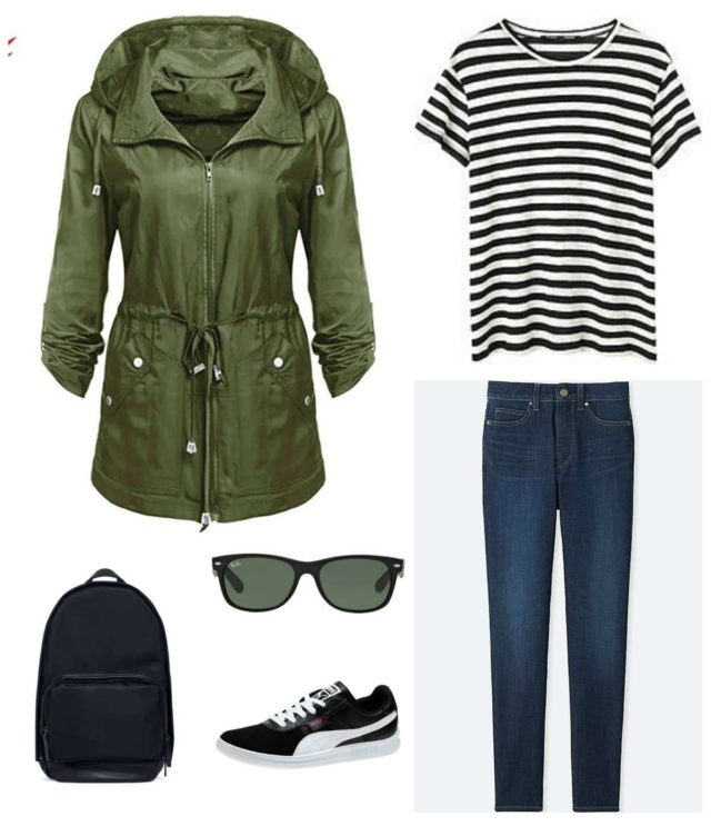 Black and white striped t-shirt with dark ankle jeans, black Puma sneakers, black Ray-Ban Wayfarer sunglasses, a black backpack, and olive anorak.
