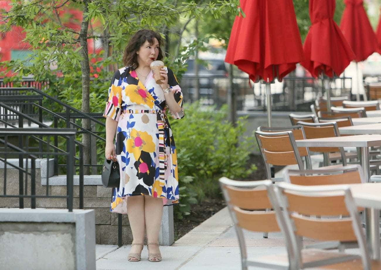 Image of a woman in a black, yellow, pink, and blue graphic printed wrap dress, holding a black handbag, wearing tan suede heeled sandals, and sipping on an iced latte. She is standing outside near chairs and tables with red umbrellas.