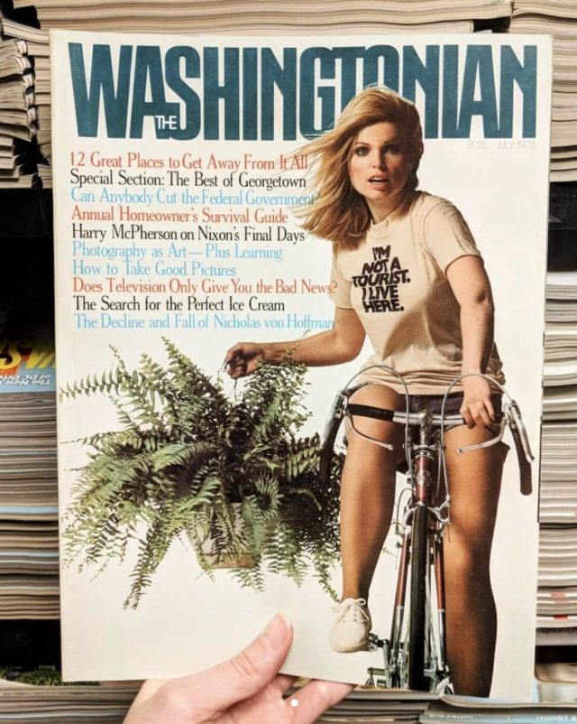 Cover of a Washingtonian Magazine. It features a blonde woman on a bicycle carrying a fern plant. She is wearing a t-shirt that says I'm Not a Tourist. I Live Here.