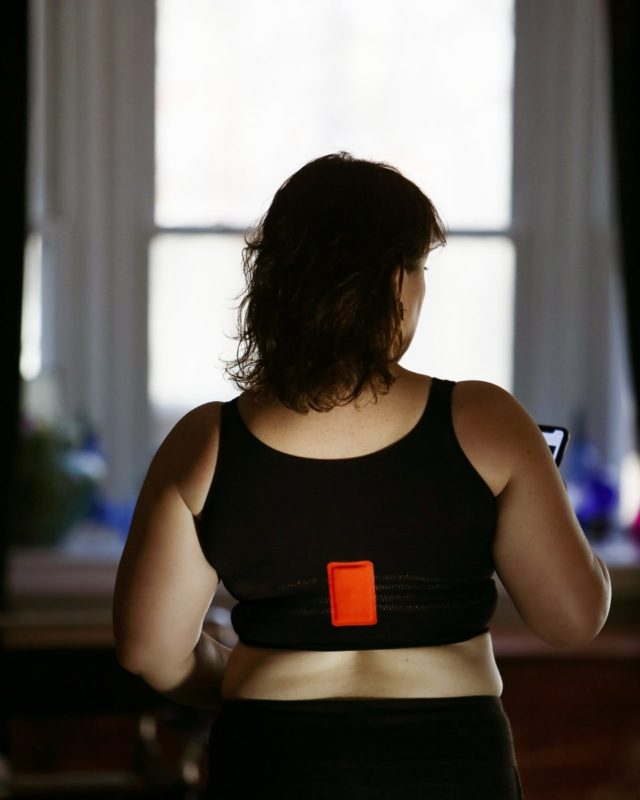The back of the Soma INNOFIT bra, showing the orange battery pack and how it fits in the middle of the back