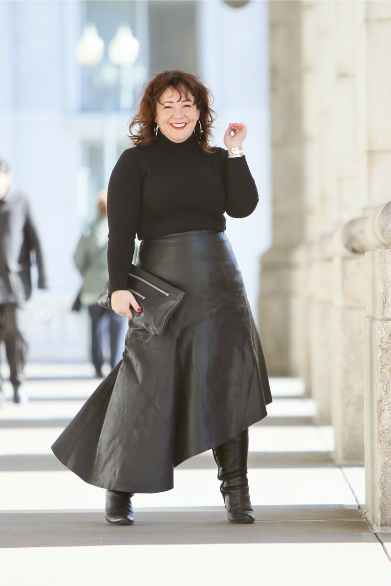 Wardrobe Oxygen in a black cashmere turtleneck, black leather asymmetrical skirt from Topshop, and silver Jenny Bird Trust Hoops with black knee-high wide calf heeled boots #over40fashion #40plusstyle #petitefashionblogger