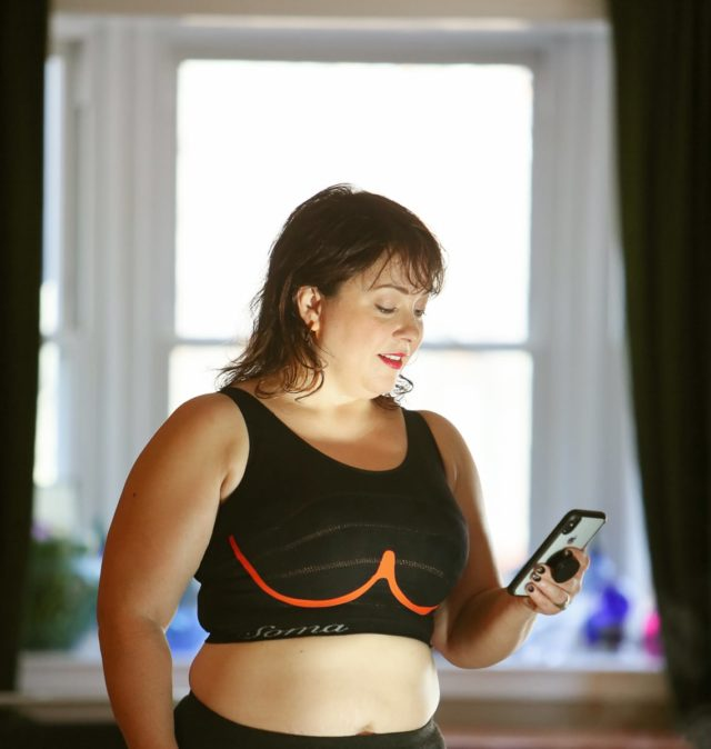 Alison wearing the Soma INNOFIT bra while looking at the INNOFIT app on her smartphone