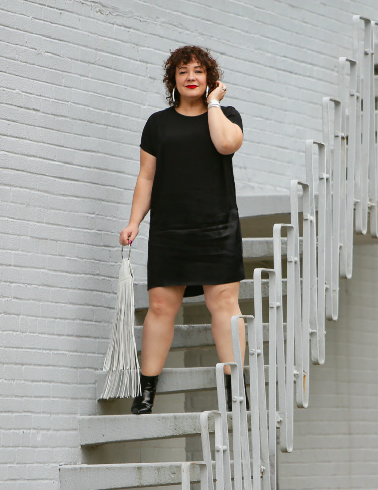 Wardrobe Oxygen in a black crepe dress from Universal Standard with a white fringe bag from KARA and black patent leather wide width ankle booties from ASOS