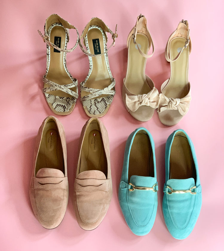 Four pairs of shoes placed on a pink background. A pair of tan suede block heel sandals with bow detail at the toes, snakeskin high-heeled sandals, blush colored suede penny loafers, and turquoise suede loafers with a gold bit detail