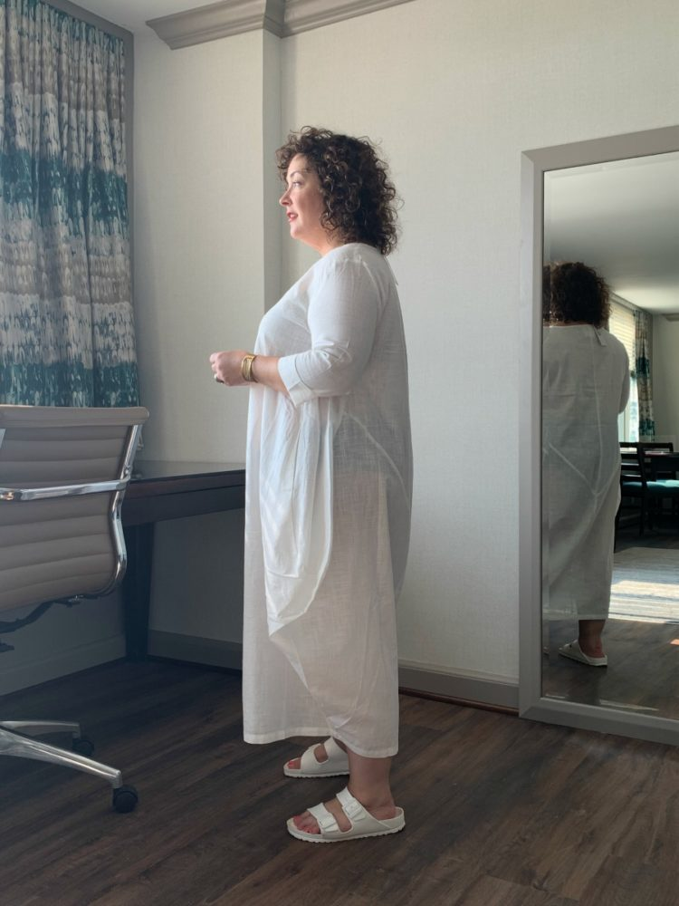 Alison Gary in an ankle-length thin cotton dress standing in profile looking out of a window for a DUBGEE by Whoopi review of the clothing line