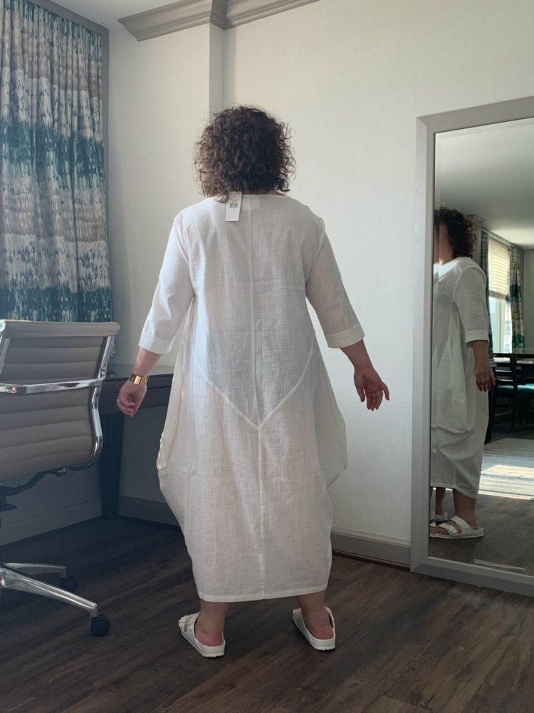 AlisoN Gary of Wardrobe Oxygen standing in a sheer white ankle-length dress, face away from the camera