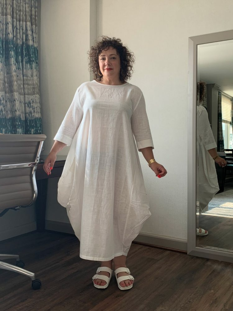 Alison Gary of Wardrobe Oxygen standing in an ankle-length loose cotton dress with elbow length sleeves. This is for a DUBGEE by Whoopi review of the clothing line