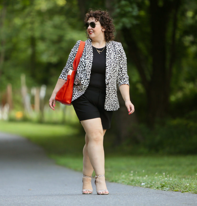 Alison wearing a leopard print blazer with a black tee and black shorts carrying an orange Clare V tote