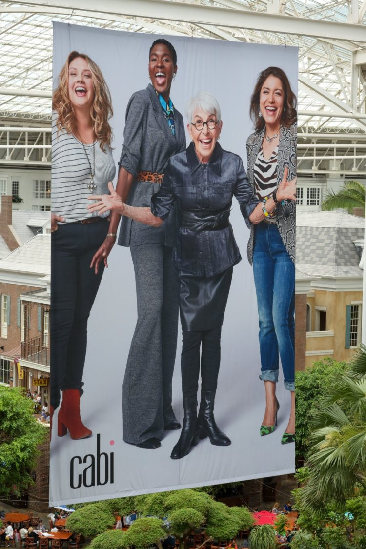 a poster depicting four women wearing cabi