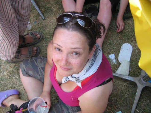 woman in pigtails sitting on the ground looking up at the camera
