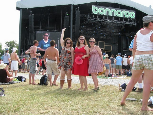 three women standing in front of a music stage at bonnaroo