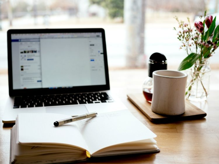 Open notebook with pen in front of open laptop with cup of coffee all on a desk in front of an open window