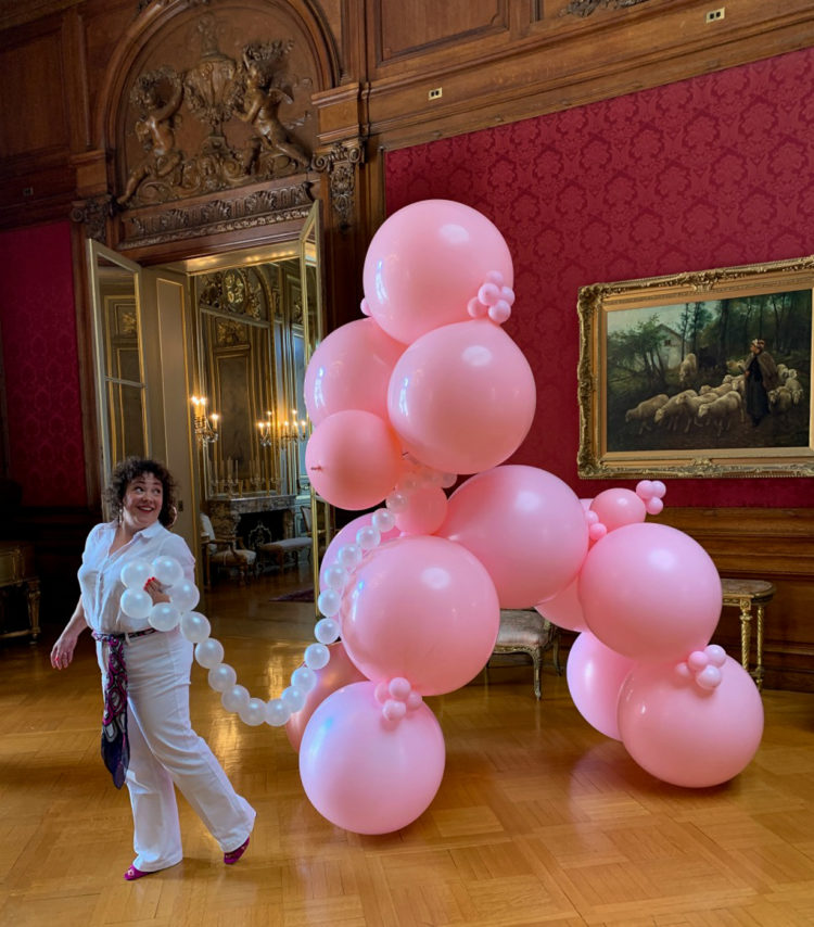 woman smiling and holding onto a chain made of balloons that is attached to a 12 foot tall pink poodle also made of balloons