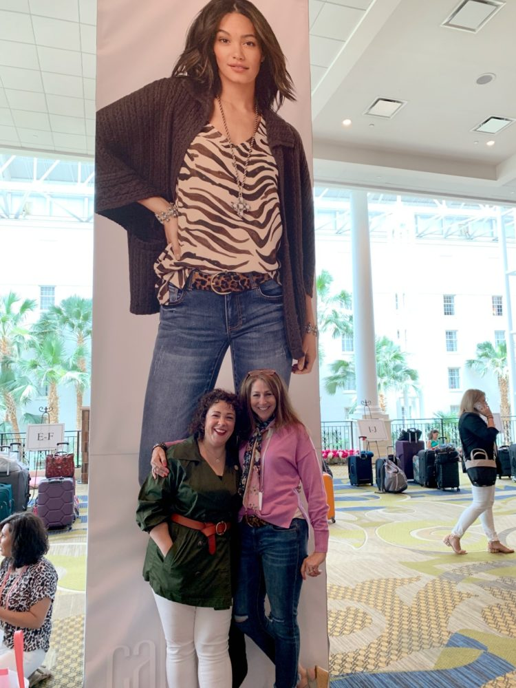 two women standing in front of a poster marketing cabi