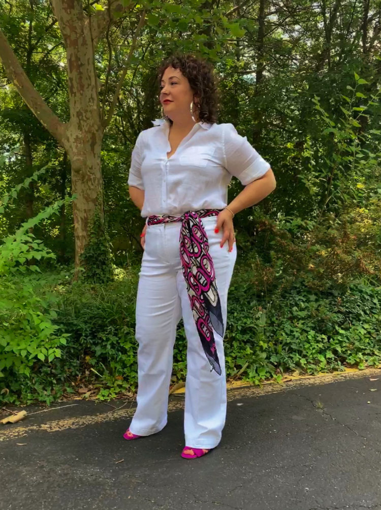 woman in white linen shirt and white wide leg jeans with a magenta and navy scarf as a belt. Her hands are on her hips and she's looking off into the distance.