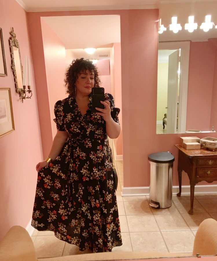 Alison Gary of Wardrobe Oxygen in a navy floral wrap midi dress taking a mirror selfie in a pink room