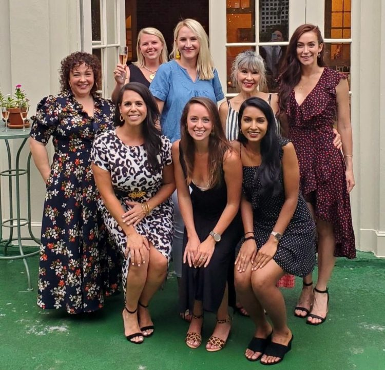 Eight women at the City Tavern Club on the terrace grouped together and smiling for the camera