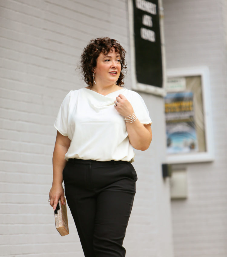 Woman in the Universal Standard Viva Boatneck Top in white with black tux-inspired ankle pants from Talbots.