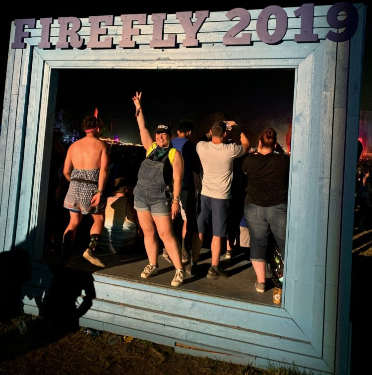 woman in shortalls giving the peace sign while standing on a stage that says FIREFLY 2019