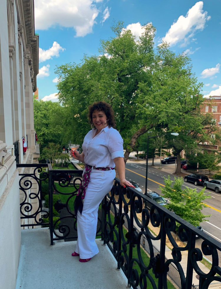 woman in all white leaning against a balcony railing in washington DC, holding a glass of champagne and smiling.