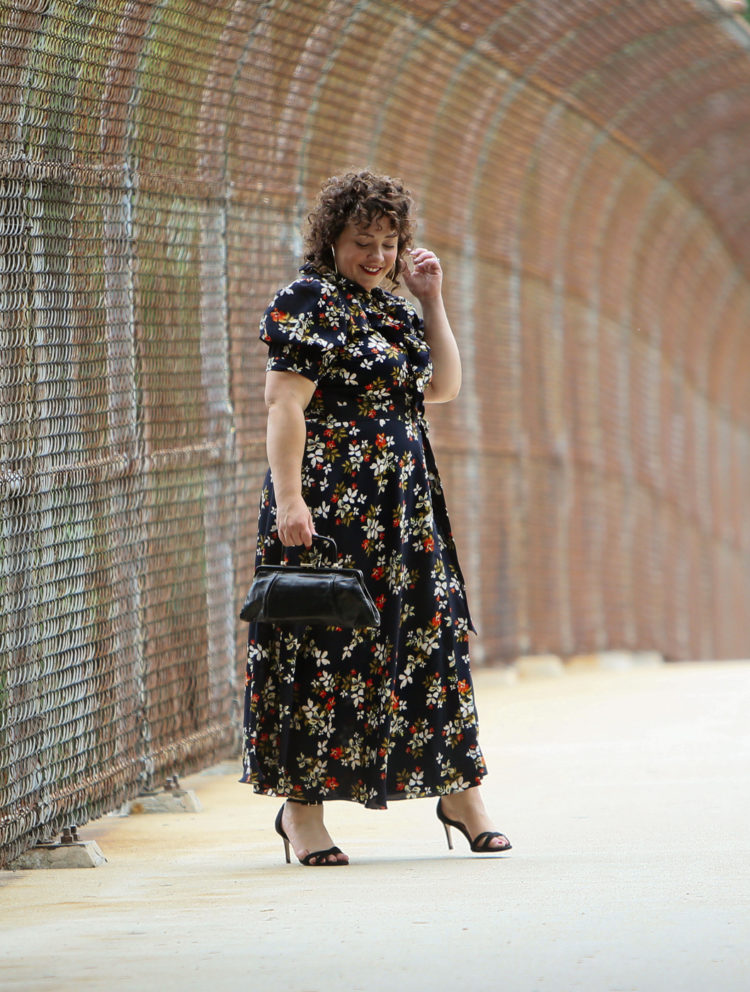 Woman in a navy floral midi length wrap dress holding a black leather vintage frame purse walking and looking at the ground