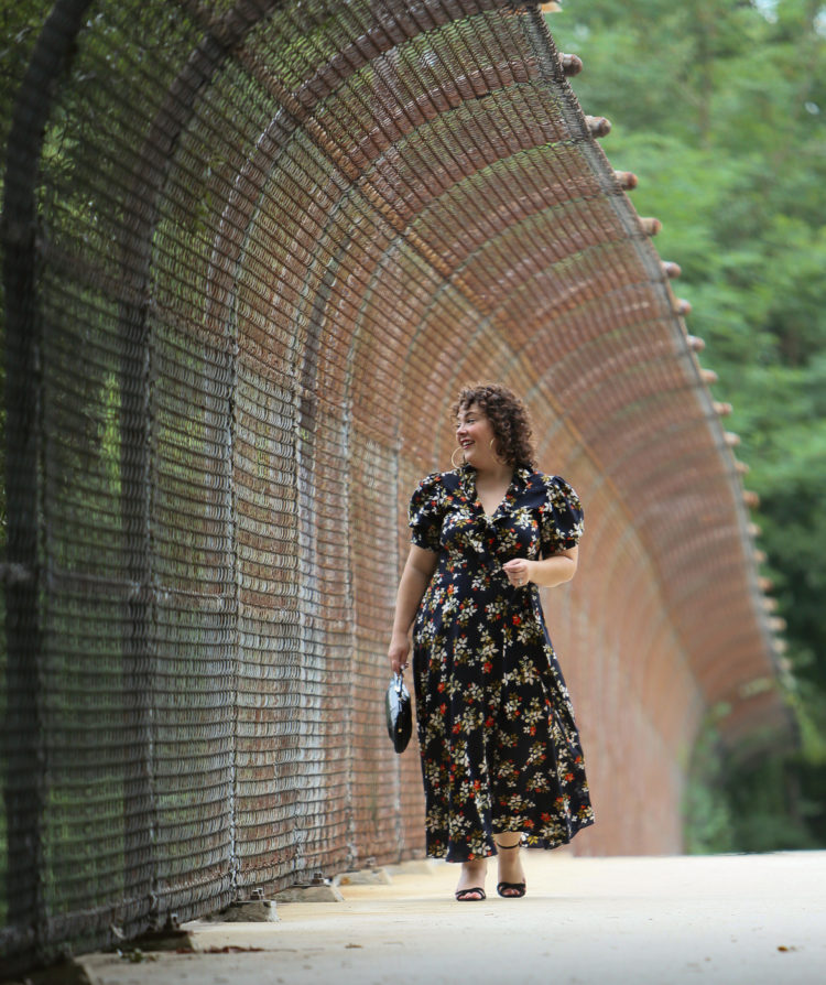 woman in a navy floral midi wrap dress walking along a city overpass looking to the side